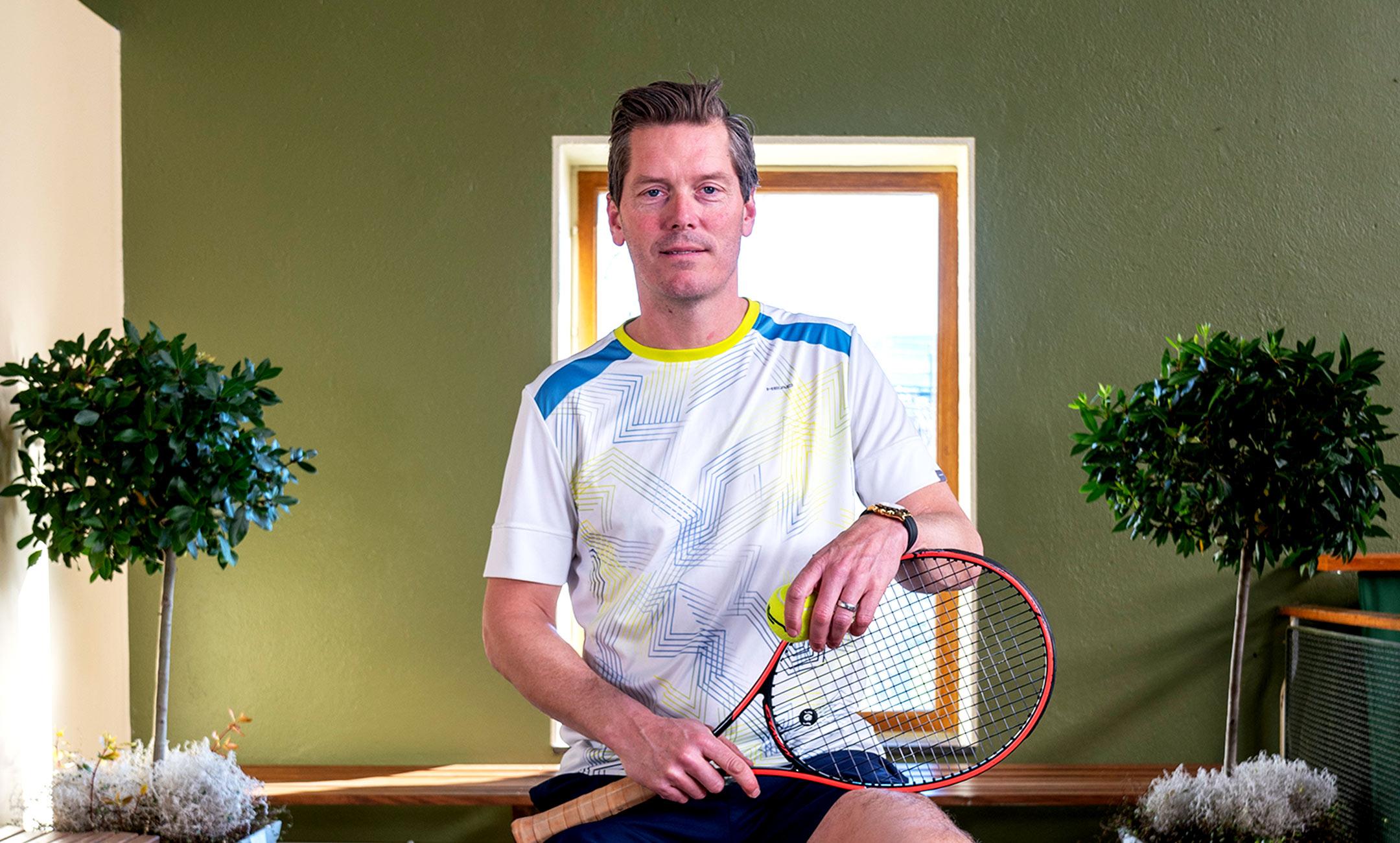 Thomas Enqvist sitter på en pall hållandes i ett tennisracket